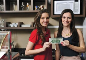 Photo with two employees holding a $100 bill